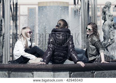 Goup of teenage girls sitting against a city fountain