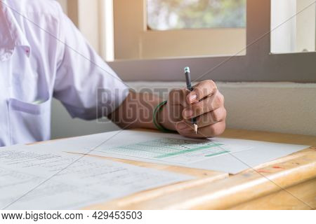 Test In School, Writing Of Student Exam For Admission Exercise In Exams Answer Sheet On Desk At High