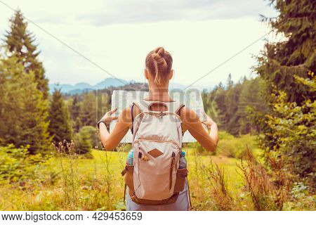 Hiking Young Woman Traveler With Backpack Checks Map To Find Directions In Wilderness Area, Real Exp