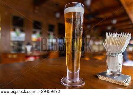 A Close Up Of A Half Empty Pint Of Fresh Draft Beer.  A Glass Of Beer On A Wooden Table In An Irish