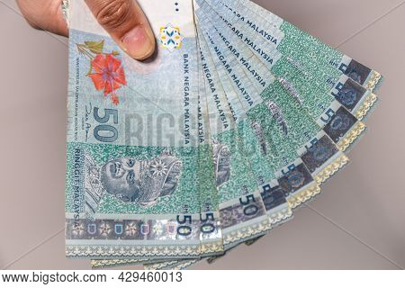 A Collection Of Fifty Malaysian Ringgit Banknote In A Female Hand. Woman Hand Show Malaysia Ringgit