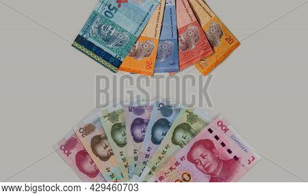 Detailed Close Up To The Chinese And Malaysian Currency On White Grey Background. Fan Of Malaysia Ri