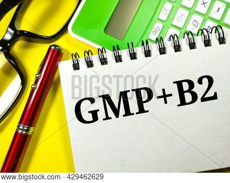 Business Concept.text Gmp+2 Writing On Notebook With Pen,glasses And Calculator On A Yellow Backgrou