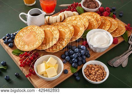 american pancake board with berries maple syrup butter