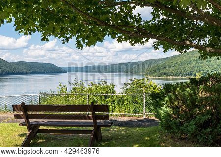A Wooden Park Bench In Mead Township, Pennsylvania, Usa Overlooking The Allegheny Reservoir In The A