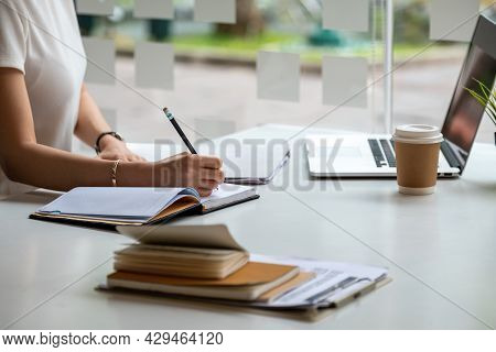 Close Up Asian Female Is Taking Notes On Her Notebook For Online Classes, Study Ideas And Note-takin