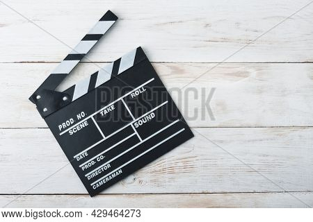 Classic black movie clapper board on white wooden background