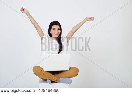 Woman Sitting Using Laptop Sitting On Gray Background