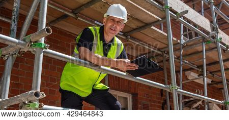 Panoramic web banner header of male builder foreman, construction worker, contractor or architect on building site writing on black clipboard panorama