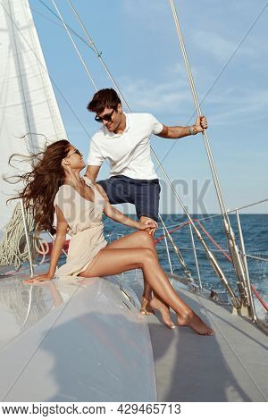 Pleased young beautiful couple resting on yacht in sea or ocean. Luxury boat. Concept of romantic relationship and enjoying time together. Sailing vacation or tourism on sea. Summertime. Sunny daytime