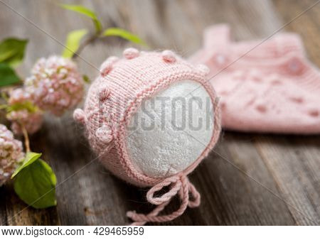 Knitted white clothes composition for newborn on the wooden table with flowers. Infant woolen clothing design set with hat