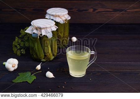 Pickled Cucumbers In A Jars, Pickle Juice In Glass Mug On A Dark Wooden Background. Homemade Marinat