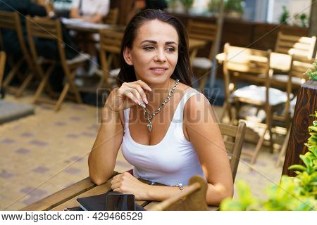 Satisfied Young Woman In White T-shirt Sits At Table Of An Outdoor Street Cafe. Distant Work. Attrac