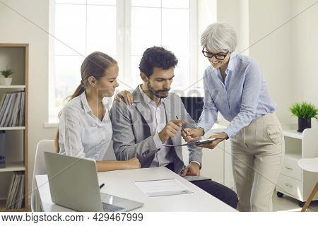Couple Signing Document During Meeting With Banking Agent, Realtor Or Mortgage Broker