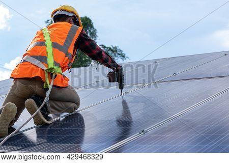 Solar Panel Technician With Drill Installing Solar Panels On Roof At Solar Panel Field,environmental