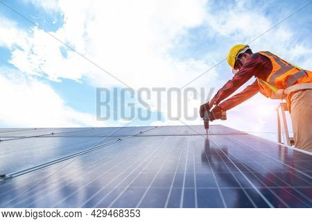 Solar Panel Technician With Drill Installing And Maintenance Solar Panels On Roof At Solar Power Pla