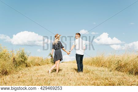 Young Couple In Love Is Walking In Field Holding Hands, Man And Young Woman In Straw Hat And Summer
