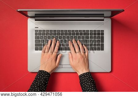 First Person Top View Photo Of Hands Typing On Laptop Keyboard On Isolated Red Background