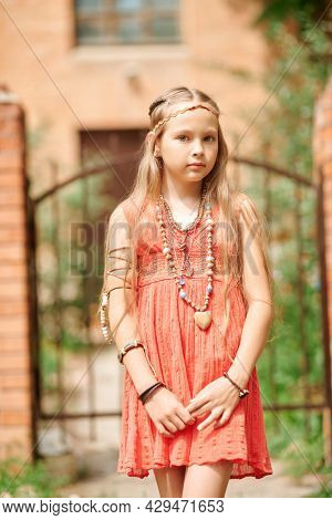 Portrait of a cute girl child dressed in hippie style posing against the background of gates near the house. Romantic hippie style.