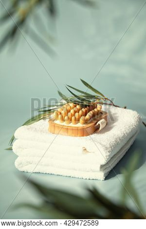Massage wooden brush on white spa towels with eucalyptus leaves pastel blue background, anti-cellulite massage and body care concept
