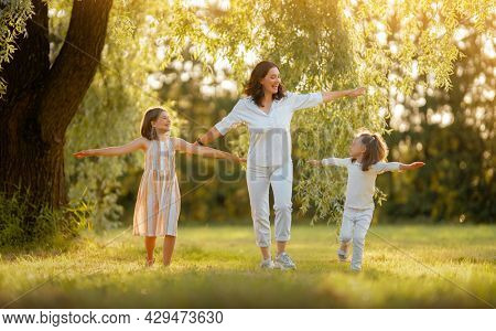 Happy family at sunset. Mother and children are running, having fun and enjoying summer evening.