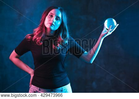 Mysticism And Divination Concept. Woman In Colorful Neon Lighting On Dark Background.
