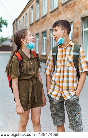 Schoolboy and schoolgirl posing on the way to school. They play, laugh and fool around. Wearing a protective mask on their faces from a coronavirus infection. Education and back to school concept.
