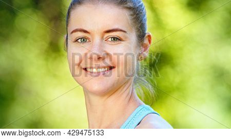 Sportive young woman blonde in blue tracksuit turns head and looks straight with cheerful smile