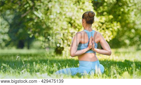 Young woman with hair bun in blue tracksuit practices yoga pose joining hands on back on green lawn
