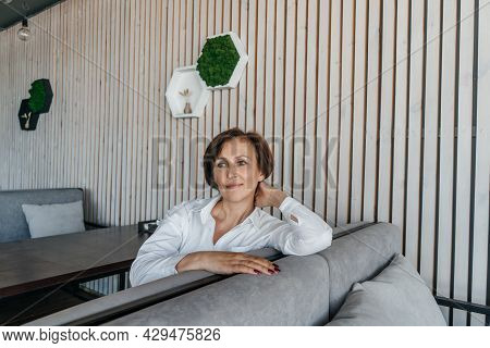 Senior Businesswoman Have A Rest In Cafe.