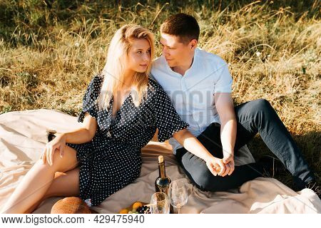 Happy Young Couple Hold Hands And Look At Each Other While Relaxing, Romantic Picnic On The Lawn Wit