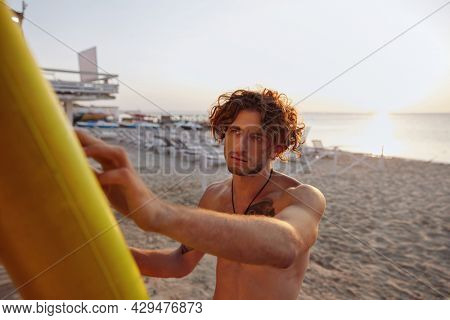 Young european surfer looking something on his surfboard. Concentrated curly man with tattoo. Concept of extreme water sport. Idea of summer vacation. Sandy beach coast. Sunny daytime