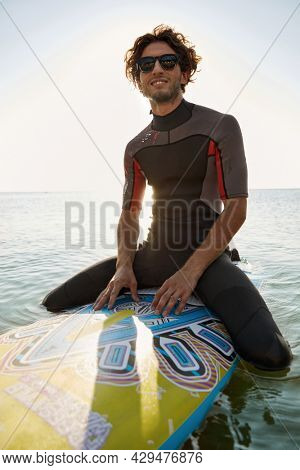 Young surfer sitting on surfboard in sea water. Enjoying curly man wear diving suit and glasses. Concept of extreme water sport. Idea of summer vacation. Sunny daytime