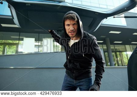 Aggressive european robber looking in car trunk. View from auto trunk with human victim. Male bearded bandit wear black hoodie and gloves. Concept of kidnapping. City daytime
