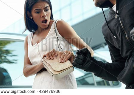Angry robber want to steal handbag of frightened girl. Obscure face of man want to punch young woman. Male bandit wear black hoodie. European people near automobile. Concept of robbery. City daytime