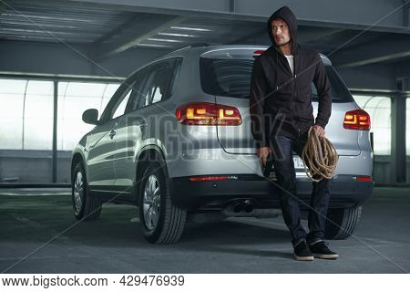 Focused caucasian robber standing near private automobile. Male bearded bandit wear black hoodie and hold pistol with rope. Concept of robbery and kidnapping. Inside parking lot
