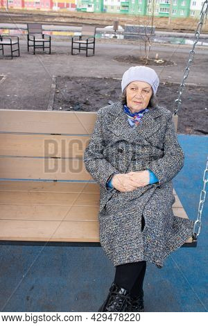 Sad Old Woman On A Fresh Street. A Lonely Old Woman Sits On A Swing. Sad Elderly Woman In The City.