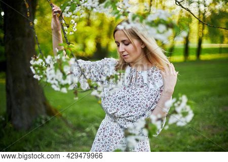 A Girl With Blonde Hair In A Flower Dress Stands Next To A Flowering Tree