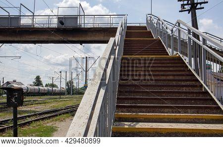 Railway Bridge With Steps, With Impressive Steps In Perspective. Overhead Pedestrian Crossing. Bridg
