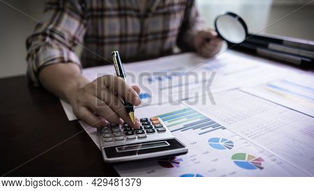 Accountants Or Auditors Using Calculator And Holding Magnifying Glass.