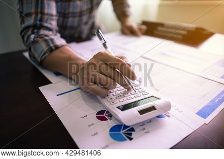 Business Accounting, Businessman Using Calculator And Reading Statistic Report With Budget And Loan