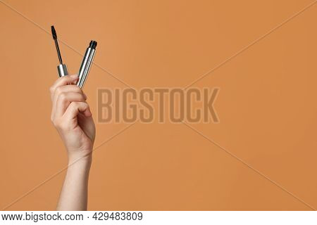 Woman Holding Mascara On Light Brown Background, Closeup. Space For Text