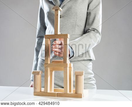 Business Woman Building Tower On Table From Wooden Blocks. Strategy Planning And Development Concept