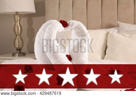Five Star Luxury Hotel. Beautiful Swans Made Of Towels Decorated With Red Roses On Bed In Five Star