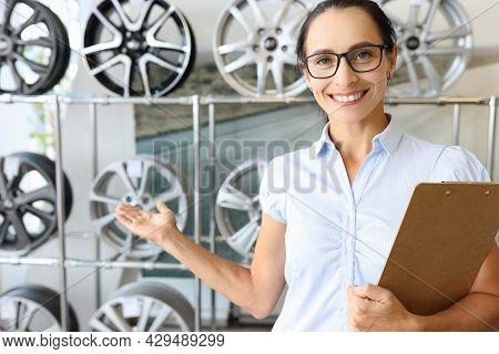 Smiling Female Consultant Recommends Car Rims Closeup
