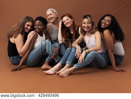 Six Women Of Different Ages Sitting Together In Studio On Brown Background. Multi-ethnic Group Of Di