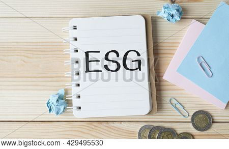 Esg Finance Write On Book Isolated On Wooden Table. Medical Or Finance Concept