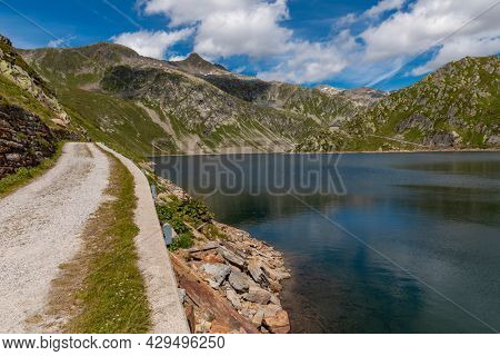 Panorama from the Gotthard pass in Ticino of the Swiss Alps on a summer's day with sunshine and blue skies. In the water there are ripples and reflections of the mountains.