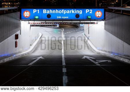 Underground car park entrance with german inscriptions in Luzern. Night view, illuminated by lights. Street signs on the ground. Nobody inside