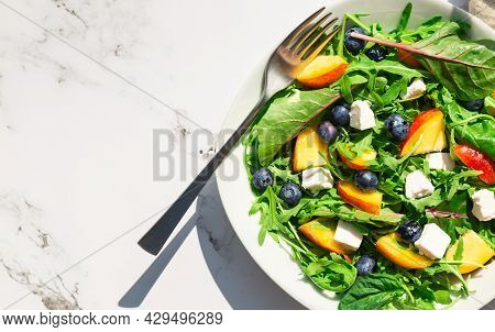 Fresh Homemade Salad With Nectarines, Blueberries, Arugula, Spinach And Feta Cheese On White Marble